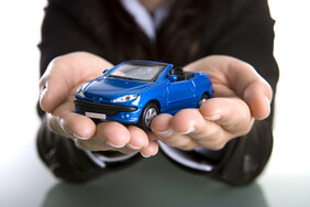 Person holding a toy car in his palm