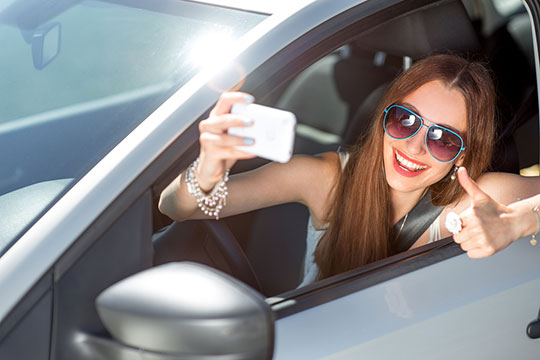 Woman taking selfie in car