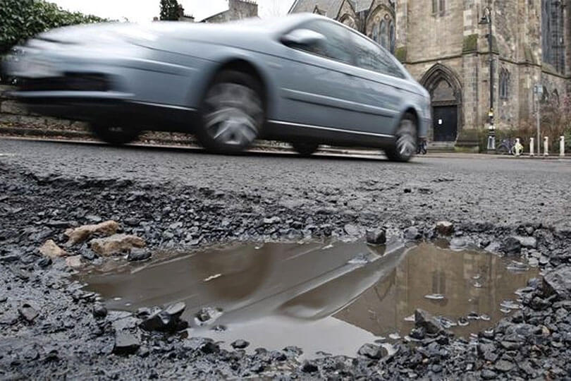 Car driving past pothole