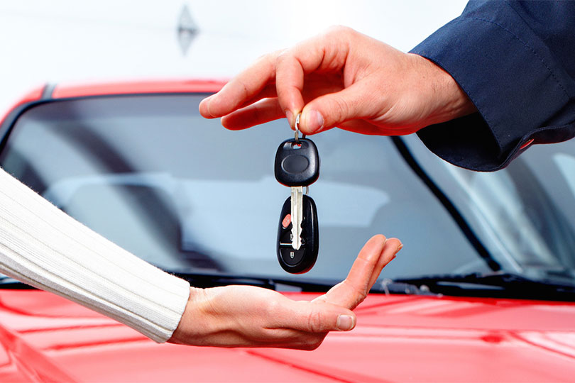 Man handing woman car keys