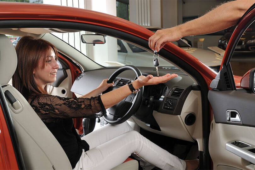 Woman holding out hand for keys to her new car