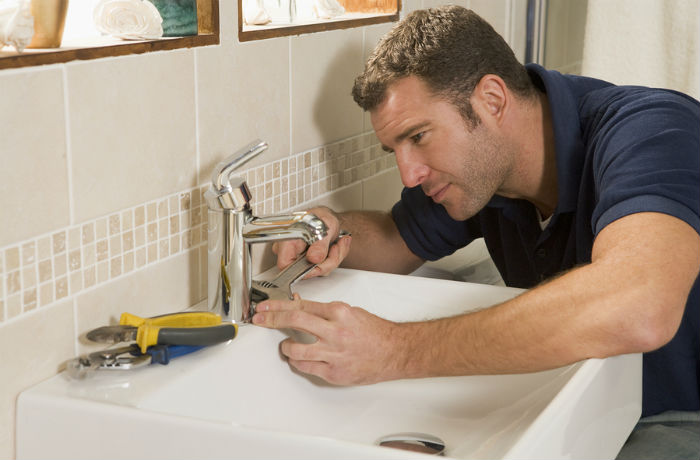 Plumber fixing the sink