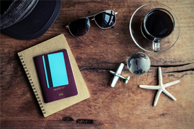 A rustic desk with coffee, sunglasses, a notebook and a passport