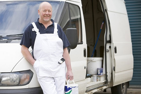 Painter decorator stood beside a white van